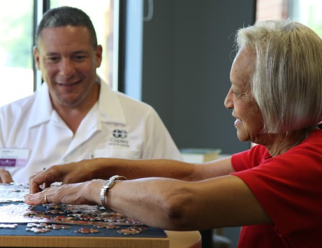 senior doing puzzle with senior living employee
