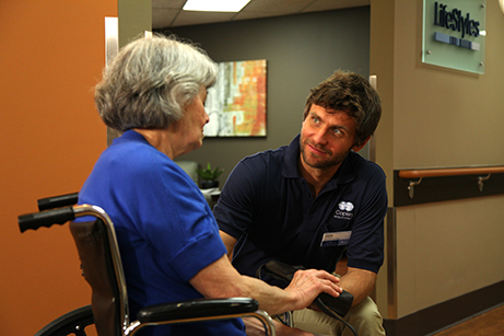 An assisted living caregiver talks to a female resident in a wheelchair