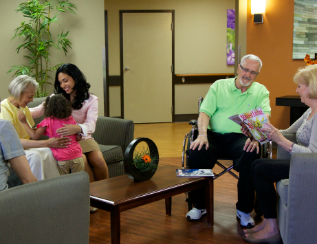 A group of family members meet with CommuniCare guests in the lobby.